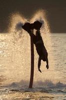 Flyboarder streckt sich nach dem Backflip in Richtung Wellen foto