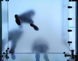 Füße von Menschen, die auf durchscheinendem Glas stehen foto
