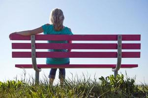 Frau in Blau sitzt auf einer rosa Bank im ländlichen Bereich