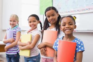 niedliche Schüler, die während der Klassenpräsentation in die Kamera lächeln foto