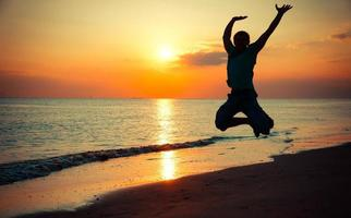 glücklicher Mann sprang in der Luft im Sonnenuntergang am Strand foto