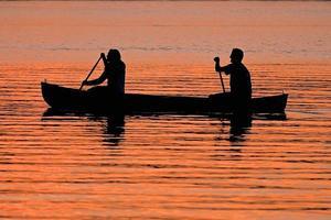 Paar Kanufahren während des Sonnenuntergangs foto
