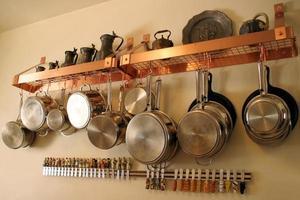 Nahaufnahme von Metalltöpfen und -pfannen, die an der Küchenwand hängen foto
