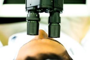 Stirn eines Forschers, der mit einem Mikroskop arbeitet foto
