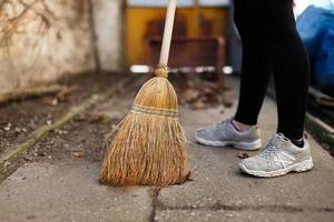 Frau fegen Blätter und Erde in Mülleimer