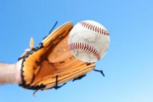 Person, die Baseball mit blauem Himmelhintergrund fängt foto