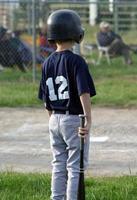 junger Spieler wartet auf Fledermaus foto