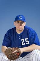 Baseballspieler kauert auf dem Spielfeld foto