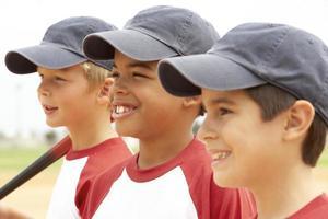 Drei Jungen in einer Baseballmannschaft stehen in einer Reihe