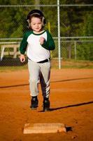 Kind läuft Basen beim Baseball spielen foto