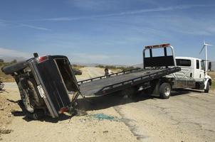 Mann, der sich vorbereitet, abgestürztes Auto auf Abschleppwagen zu heben foto