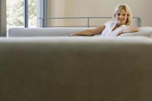 Frau, die auf Sofa zu Hause entspannt, lächelt, Fokus auf Hintergrund foto