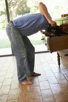 Mann auf der Suche nach etwas in Schubladen foto