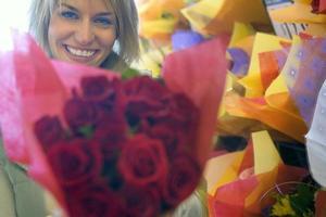 Frau, die Rosenstrauß neben Ladenausstellung in Floristen hält, foto