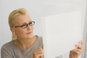 Nahaufnahme einer Geschäftsfrau, die eine Blaupause betrachtet foto