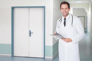 zuversichtlicher Arzt, der Akte im Krankenhauskorridor hält foto