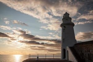 Leuchtturm und Sonnenuntergang am Meer foto