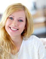 fröhliche blonde Frau, die Kamera betrachtet