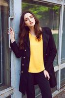 junge Frau im schwarzen Trenchcoat und in der gelben Bluse foto