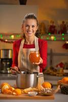 Porträt der lächelnden jungen Hausfrau, die hausgemachte orange Marmelade zeigt foto