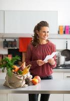 Porträt der glücklichen Hausfrau, die Lebensmitteleinkaufschecks hält foto
