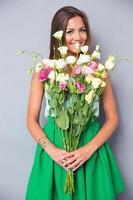 fröhliche Frau, die Blumen hält