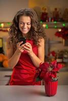 glückliche junge Hausfrau, die SMS in der weihnachtlich dekorierten Küche schreibt