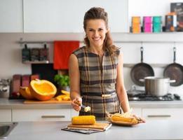 glückliche junge Hausfrau, die gekochten Mais mit Butter reibt foto
