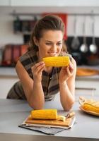 Porträt der glücklichen jungen Hausfrau, die gekochten Mais in der Küche isst foto