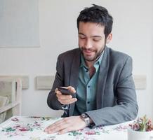 junger Mann, der Jacke trägt, die im Restaurant sitzt foto