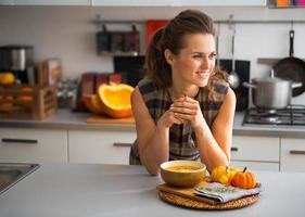 junge Hausfrau, die Kürbissuppe in der Küche isst foto
