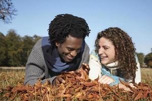 fröhliches Paar, das im Feld liegt foto