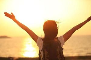jubelnde wandernde Frau Sonnenaufgang am Meer foto