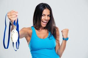 fröhliche Fitnessfrau mit Medaille foto