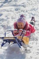 fröhliches Kind auf einem Schlitten