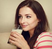 lächelnde Frau, die Milch trinkt und glücklich aussieht. Nahaufnahmeporträt foto