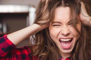 fröhliche Frau, die ihre Haare berührt foto