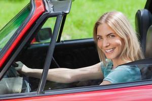 fröhliche Frau, die rotes Cabriolet fährt