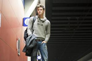 schöner junger Mann, der im Zug oder in der U-Bahnstation steht