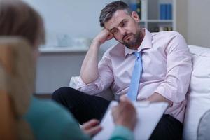 Verzweiflungsgeschäftsmann während der Psychotherapie foto