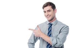 fröhlicher junger Mann, der auf etwas zeigt foto