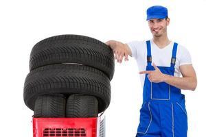 fröhlicher Mechaniker zeigt in neue Reifen