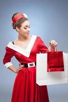 fröhliches Retro-Mädchen, das Einkaufstaschen hält foto