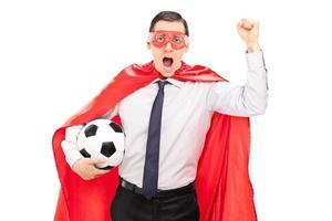 Superheld jubelt und hält einen Fußball