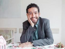 glücklicher junger Mann, der Jacke trägt, die im Restaurant sitzt und lächelt. foto