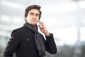 junger Geschäftsmann, der auf Handy spricht foto