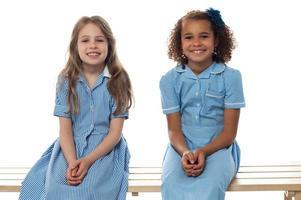 fröhliche Kinder, die sich auf der Schulbank entspannen foto