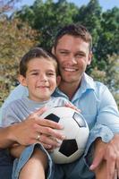 fröhlicher Vater und Sohn mit Fußball foto