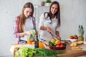 zwei Mädchen bereiten das Abendessen in einem Küchenkonzept vor, das kulinarisch kocht foto
