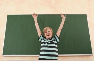 Junge jubelt vor Tafel foto